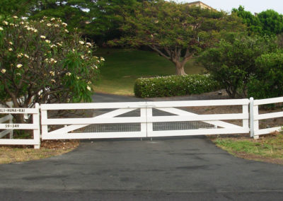 A white three rail double gate and fence surrounded by trees.