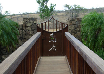 Metal Japanese gate with Japanese characters, walkway and railing.