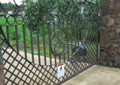 Detail of a metal gate with S design, mesh and swirls