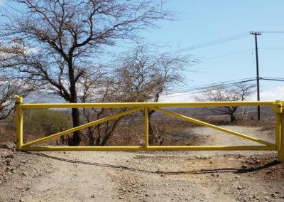 Yellow barrier arm gate across dirt road.