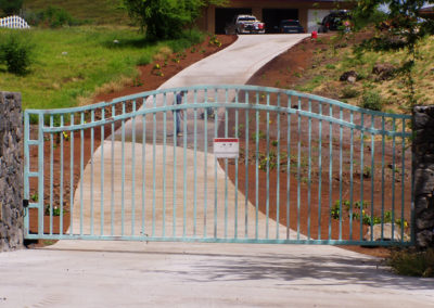 A weathered copper arched metal gate over a driveway.