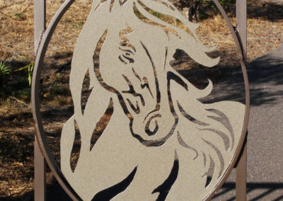 A metal horse head art work on a gate