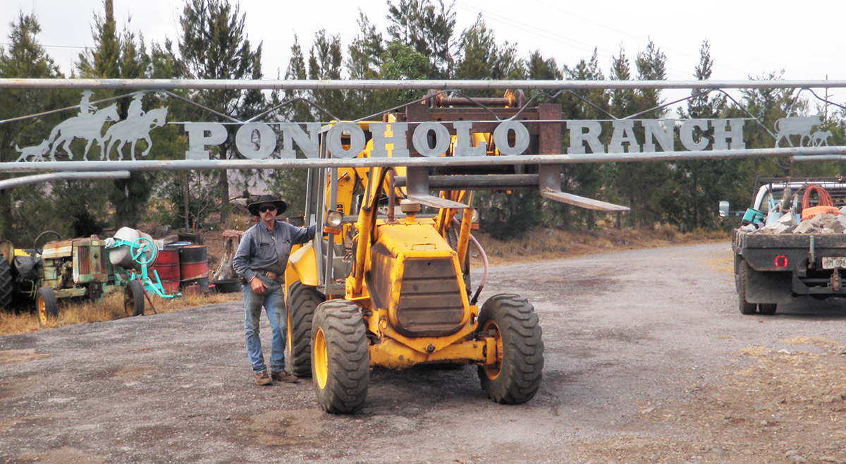 Jeff Hanneken stands with yellow JCB tractor holding Ponoholo Ranch metal sign