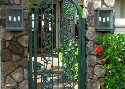 A green pedestrian gate with flowers and vines in metal.