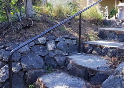 Custom built black hand rail down stone steps.