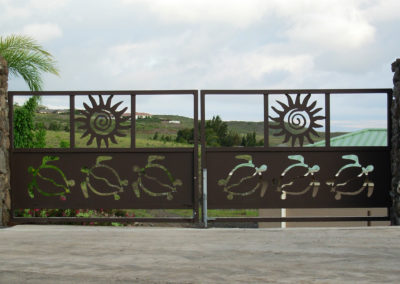 Large double gate with turtle and sun designs.